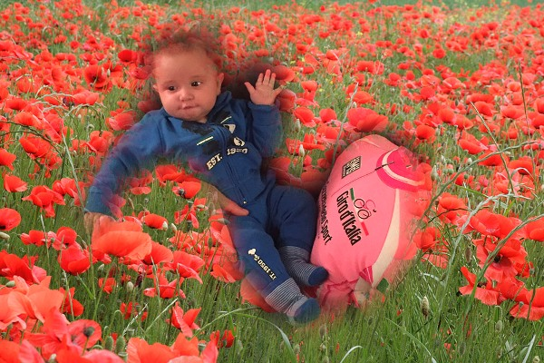 """Il piccolo Matteo tra i fiori, i colori ed un gadget del Giro firmato """"Gandini Activ Group"""" (Foto di Antonio Pisoni)"""