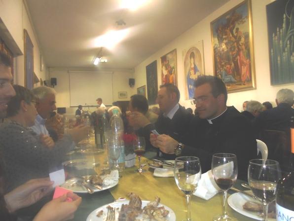 Don Daniele Laghi con i commensali del pranzo comunitario (Foto Roberto Miserocchi)